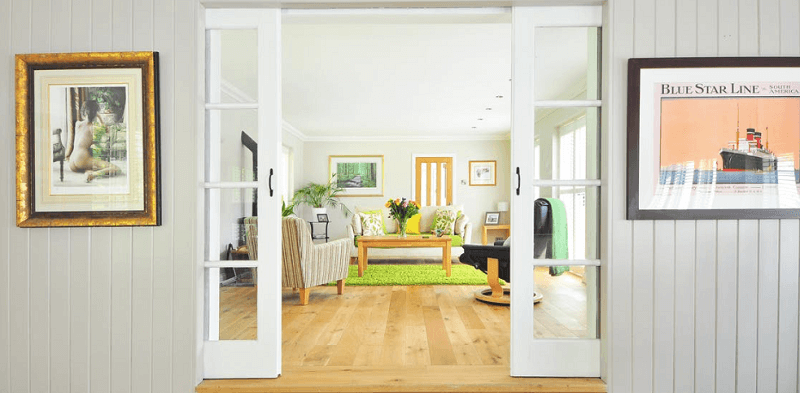 White internal doors leading into lounge with wooden floors and furniture