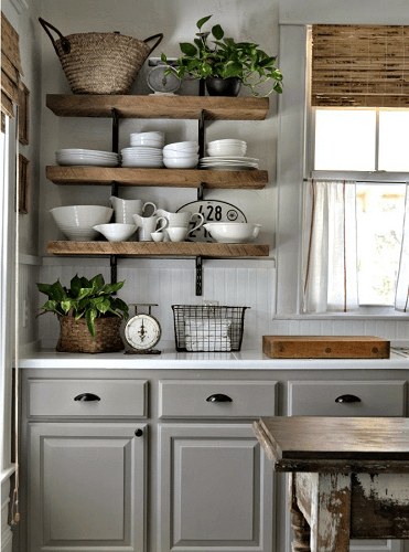 Plates stacked on wooden open shelving in traditional grey kitchen.