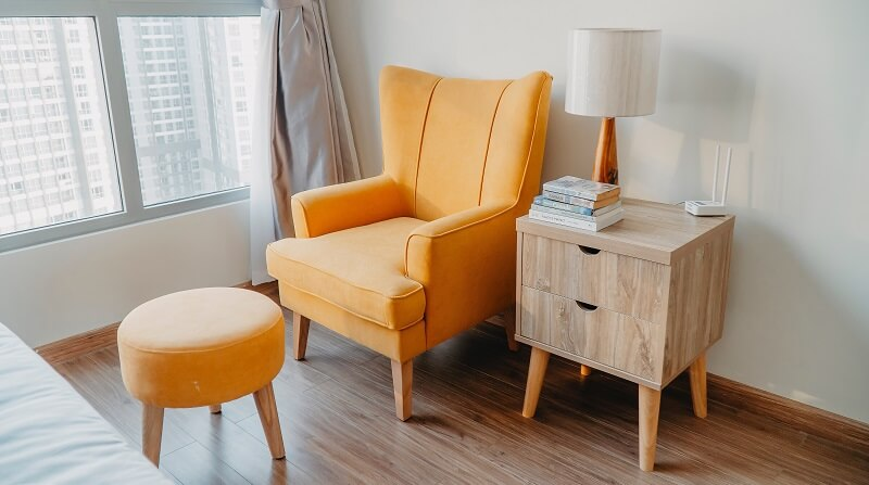 Orange arm chair and orange foot stool with small set of draws with lamp.
