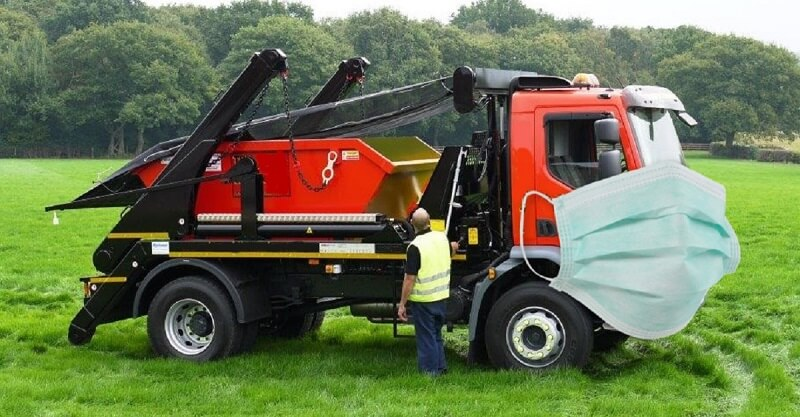 Black and red truck with a skip bin on the back. Truck is in a field with a face mask.
