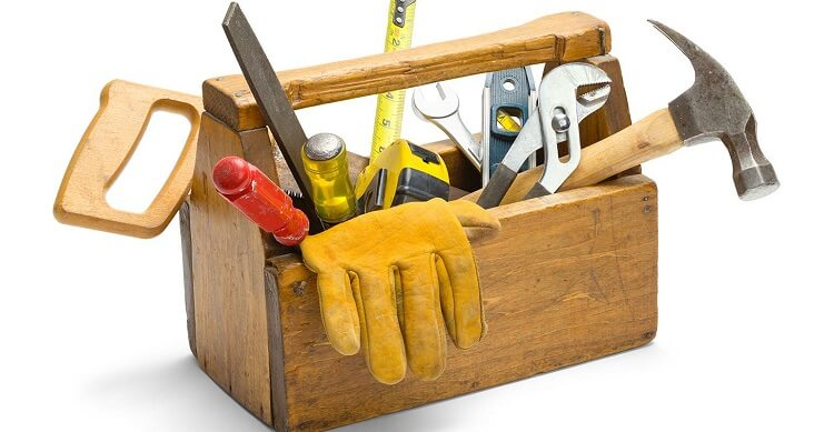 Wooden toolbox containing hammer, gloves, saw and ruler