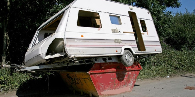 Wrecked caravan placed on top of a red skip bin