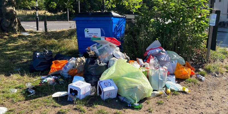 Large amount of household rubbish illegally dumped around a blue commercial waste container.