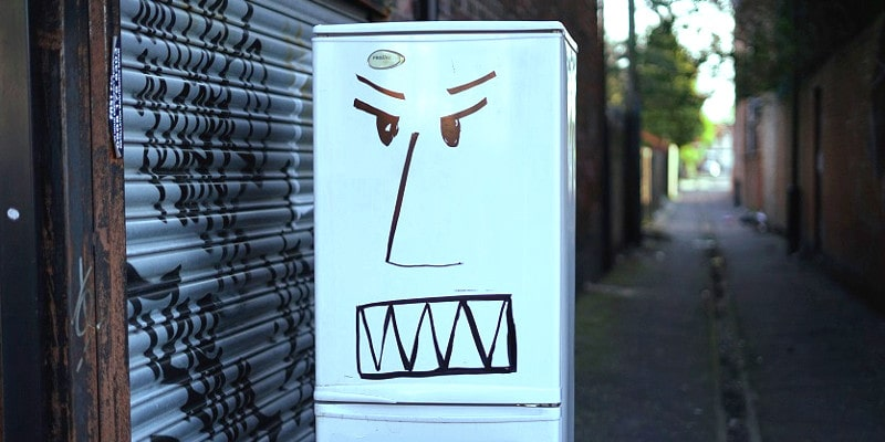 White fridge placed in the middle of a city service lane. Fridge has an angry face drawn on it.