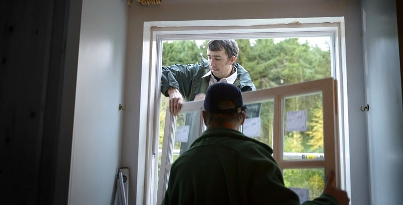 Two builders add a new window into a house.