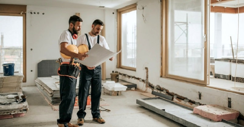 Two male builders looking at building plans inside a partially renovated room