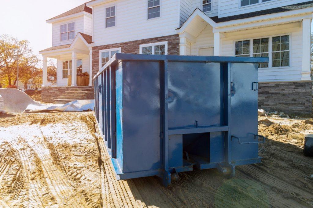 Large blue skip bin outside white house under construction